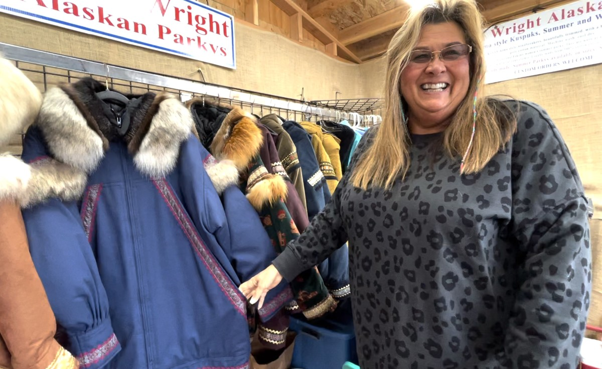 Sheila Ezell laughs as she explains that she puts a smaller hand-warmer pocket inside the big one on her parkas for people like her who always forget to grab their mittens. At the Alaska State Fair Sept. 5, 2021 (Photo from video by Joaqlin Estus, Indian Country Today).