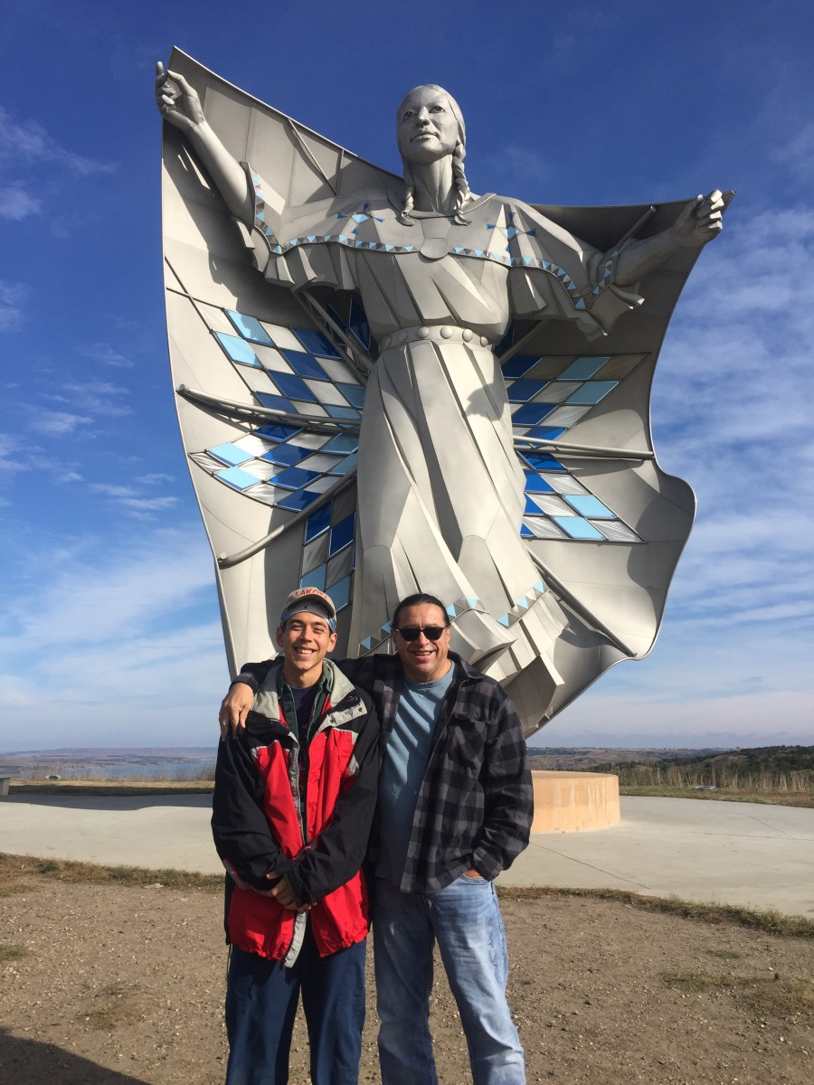 Mato Wayuhi, government name Mato Standing Soldier, and his dad, Michael Standing Soldier, in front of the 50-foot Dignity statue of Chamberlain, South Dakota, in 2019. (Photo courtesy of Mato Wayuhi)